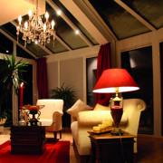 Wintergarten mit Abendbeleuchtung durch einen Kronleuchter und eine rote Stehlampe. Im Wintergarten befindet sich ein Sofa, ein Sessel und ein Couchtisch.